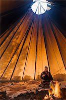 Sami reindeer herder inside his lavvu tent, Giron Siida homestead, Kiruna, arctic Sweden, Scandinavia, Europe Stock Photo - Premium Rights-Managednull, Code: 841-05797004