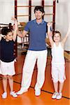 Portrait of male gym teacher with two schoolgirls raising their arms in gym Stock Photo - Premium Royalty-Freenull, Code: 618-05800326