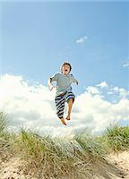 Boy leaping over grass on beach Stock Photo - Premium Royalty-Freenull, Code: 649-05800905