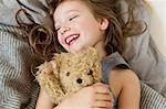 Smiling girl holding teddy bear in bed Stock Photo - Premium Royalty-Freenull, Code: 649-05801020