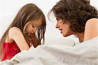 sad child sitting - Mother and daughter talking on bed Stock Photo - Premium Royalty-Freenull, Code: 649-05801027
