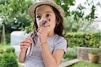 Girl smelling flower outdoors Stock Photo - Premium Royalty-Freenull, Code: 649-05801129