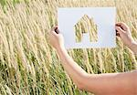 Woman holding paper house cut out Stock Photo - Premium Royalty-Free, Artist: Ikon Images, Code: 649-05801223