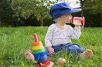 Baby drinking juice in grass Stock Photo - Premium Royalty-Freenull, Code: 649-05801457