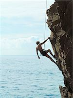 rock climber - Rock climber rappelling down rock face Stock Photo - Premium Royalty-Freenull, Code: 649-05801690