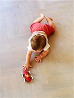 High angle view of crawling boy playing with toy car Stock Photo - Premium Royalty-Freenull, Code: 6102-05802509
