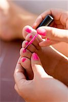 Close up of girls hand painting toenails with pink nail polish Stock Photo - Premium Royalty-Freenull, Code: 6102-05802609