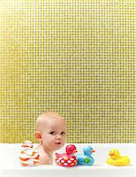 Toddler in bathtub playing with rubber duckies. Stock Photo - Premium Royalty-Freenull, Code: 6106-05810789