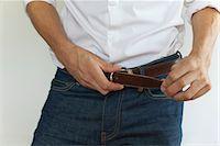 Man fastening belt, mid section Stock Photo - Premium Royalty-Freenull, Code: 632-05816224