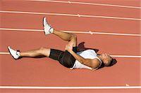 Injured runner lying on running track Stock Photo - Premium Royalty-Freenull, Code: 632-05816626
