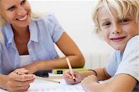Boy doing homework, smiling at camera Stock Photo - Premium Royalty-Freenull, Code: 632-05816761