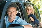 Boy riding in car with father, leaning out window and smiling at camera Stock Photo - Premium Royalty-Free, Artist: Albert Normandin, Code: 632-05816793