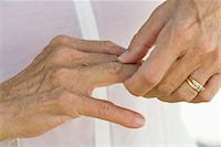 ring hand woman - Senior woman rubbing knuckles, cropped Stock Photo - Premium Royalty-Freenull, Code: 632-05817127
