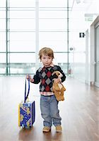 A shy boy with a soft toy and a trolley on an airport Stock Photo - Premium Royalty-Freenull, Code: 628-05817426