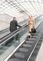 Businessman and businesswoman flirting on escalator Stock Photo - Premium Royalty-Freenull, Code: 628-05817504