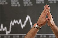 Hands of a man in front of a stock price panel Stock Photo - Premium Royalty-Freenull, Code: 628-05817598