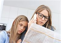 Mother reading newspaper and phoning with daughter by her side Stock Photo - Premium Royalty-Freenull, Code: 628-05817770