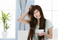 Young woman with muesli bowl disheveling her hair Stock Photo - Premium Royalty-Freenull, Code: 628-05817830