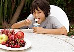 Boy eating yogurt at garden table Stock Photo - Premium Royalty-Freenull, Code: 628-05817870