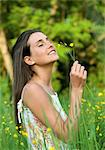 Woman in meadow smelling at flowers Stock Photo - Premium Royalty-Free, Artist: Arcaid, Code: 628-05817936