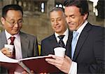 Three businessmen watching a book Stock Photo - Premium Royalty-Free, Artist: Transtock, Code: 628-05818026
