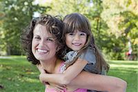 Mother carrying daughter outdoors Stock Photo - Premium Royalty-Freenull, Code: 649-05819851