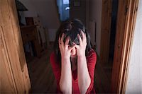 person overwhelmed stresss - Woman clutching her head in doorway Stock Photo - Premium Royalty-Freenull, Code: 649-05820643