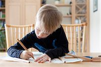 Boy drawing with colored pencils Stock Photo - Premium Royalty-Freenull, Code: 649-05820843