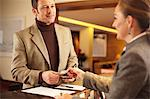Man checking in to hotel Stock Photo - Premium Royalty-Free, Artist: Michael Mahovlich, Code: 649-05821048