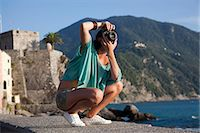 Woman taking pictures of coastline Stock Photo - Premium Royalty-Freenull, Code: 649-05821380