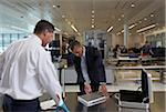 Businessman Opening Laptop for Security Guard in Airport Stock Photo - Premium Rights-Managed, Artist: Michael Mahovlich, Code: 700-05821741