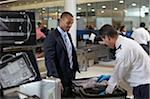 Security Guard Checking Businessman's Suitcase in Airport Stock Photo - Premium Rights-Managed, Artist: Michael Mahovlich, Code: 700-05821744