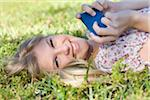 Close-up Portrait of Woman Lying on Grass holding Cell Phone Stock Photo - Premium Royalty-Free, Artist: Raoul Minsart, Code: 600-05822157