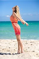 Woman Standing on Beach Feeling the Breeze Stock Photo - Premium Royalty-Freenull, Code: 600-05822160