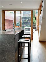 Bar stools at breakfast bar with full-height glass doors to garden, UK. Architects: STUDIO BEDNARSKI LTD Stock Photo - Premium Rights-Managednull, Code: 845-05837805