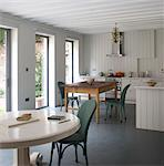 Kitchen dining room with white painted pedestal table an wood panelled walls. Architects: Chris Dyson Architects Stock Photo - Premium Rights-Managed, Artist: Arcaid, Code: 845-05838006