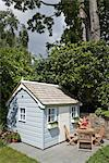 Playhouse with children's wooden dining furniture at the back of the lawn in rear garden of Irenie and Adam Cossey house in North London, UK. Designed by Modular. Photographed in June Stock Photo - Premium Rights-Managed, Artist: Arcaid, Code: 845-05838301