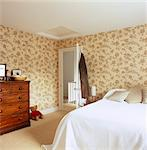Double bed and chest of drawers in bedroom with floral pattern. Designed by Designed by Clare Nash Stock Photo - Premium Rights-Managed, Artist: Arcaid, Code: 845-05838833