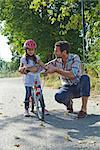 Father and daughter with helmet on bike outdoors Stock Photo - Premium Rights-Managed, Artist: F1Online, Code: 853-05840931