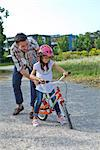 Father holding daughter on bike outdoors Stock Photo - Premium Rights-Managed, Artist: F1Online, Code: 853-05840943