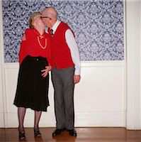 Senior couple kissing, indoors, portrait Stock Photo - Premium Royalty-Freenull, Code: 6106-05842669