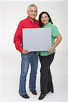 rectangle - Portrait of a mature couple holding a blank placard Stock Photo - Premium Royalty-Freenull, Code: 6106-05843480