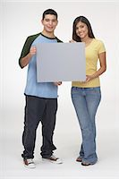 rectangle - Portrait of a teenage boy and a teenage girl holding a blank placard Stock Photo - Premium Royalty-Freenull, Code: 6106-05843571