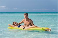 Couple relaxing in ocean, woman lying on pool raft, portrait Stock Photo - Premium Royalty-Freenull, Code: 632-05845044
