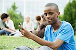 Young man with cell phone, people in background, portrait Stock Photo - Premium Royalty-Free, Artist: Kevin Dodge, Code: 632-05845103