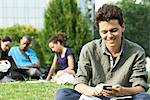 Young man text messaging with cell phone, group of people in background Stock Photo - Premium Royalty-Free, Artist: Aurora Photos, Code: 632-05845226
