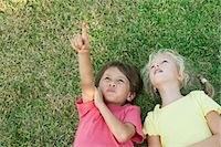 Boy and girl lying on grass, looking up and pointing Stock Photo - Premium Royalty-Freenull, Code: 632-05845241
