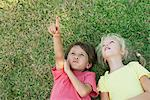 Boy and girl lying on grass, looking up and pointing Stock Photo - Premium Royalty-Free, Artist: Kevin Dodge, Code: 632-05845241