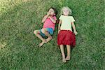 Children lying together on grass, looking up at camera Stock Photo - Premium Royalty-Free, Artist: ableimages, Code: 632-05845349