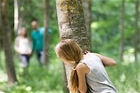 Girl hiking behind tree in woods Stock Photo - Premium Royalty-Freenull, Code: 632-05845359